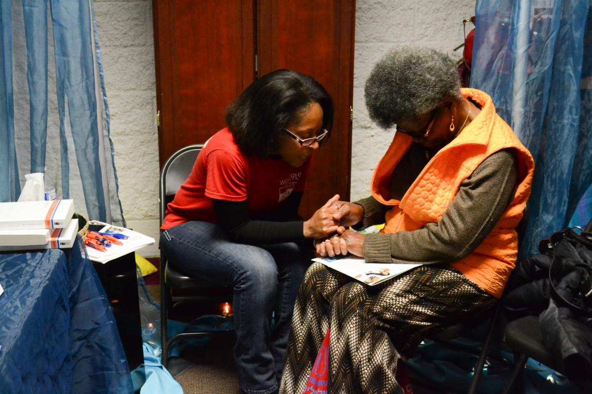 WGTS Prayer team member Gladys Guerrero prays with a listener