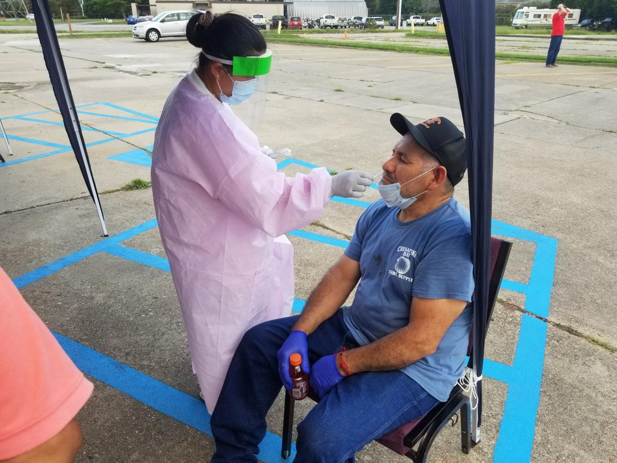 Peninsula Spanish member Domingo Flores takes advantage of the free COVID-19 test during the food bank event, administered by a local agency worker.