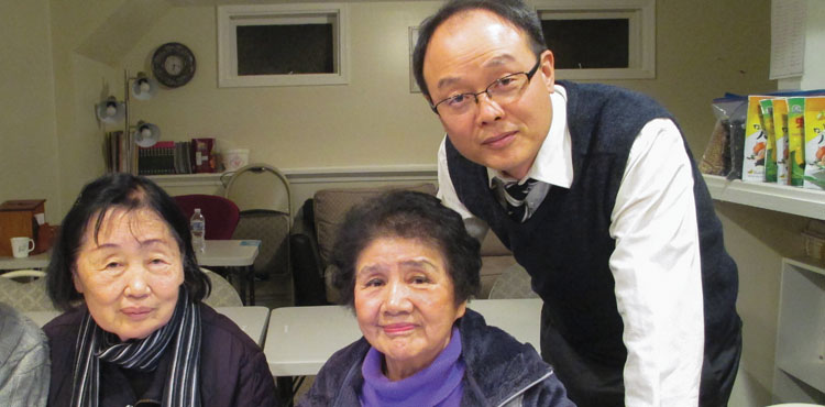 Seungho Park, pastor of Allegheny East Conference's Delaware Korean church in Newark, assists Susie Ra and Myungja Kim during a computer class held at the church's community center.