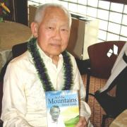Vernon Luthas, MD, is pictured holding a copy of his autobiography And the Mountains Stood Aside.