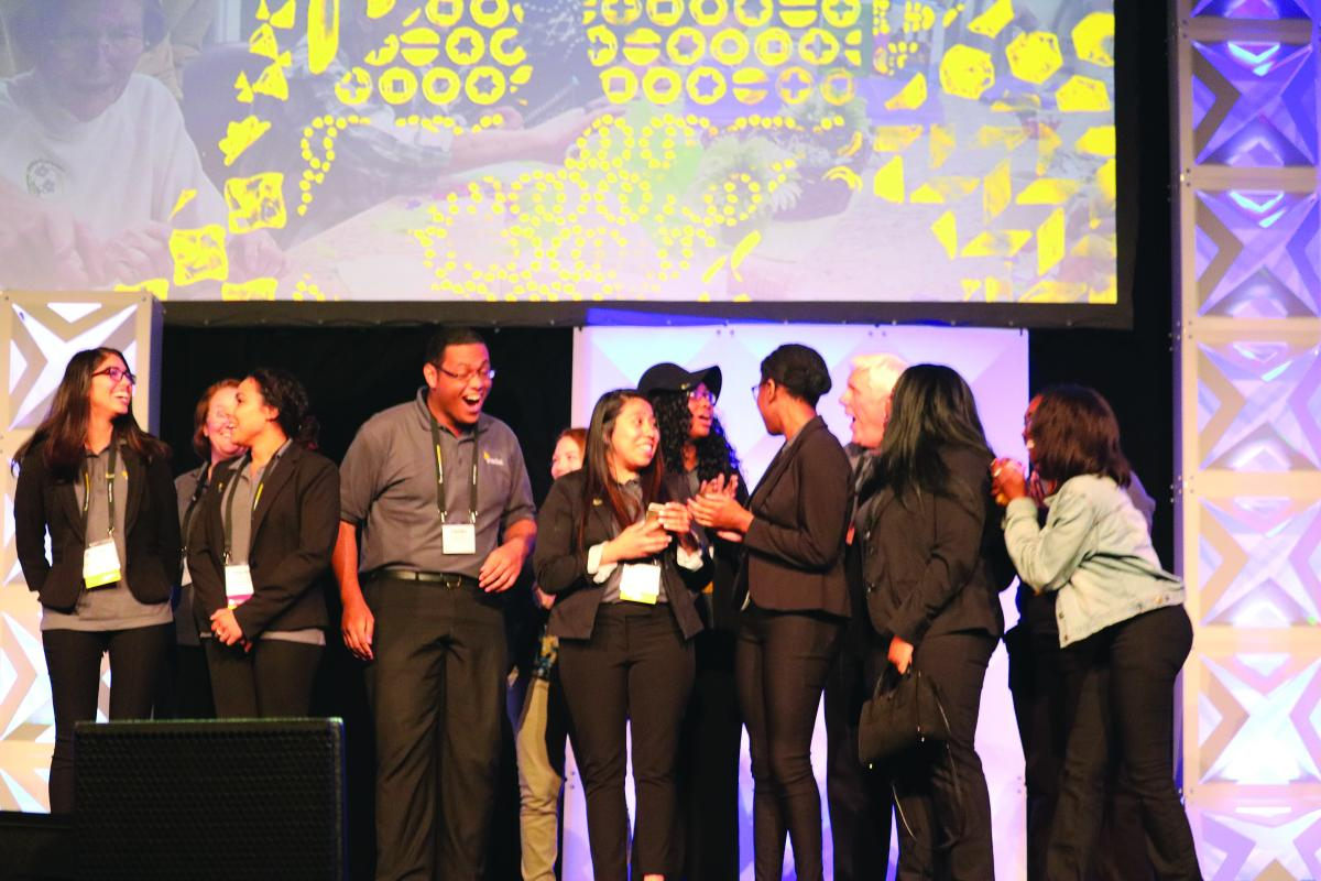 Students celebrate their first place trophy for Sam's Club Step Up for Small Business award at the Enactus USA Expo