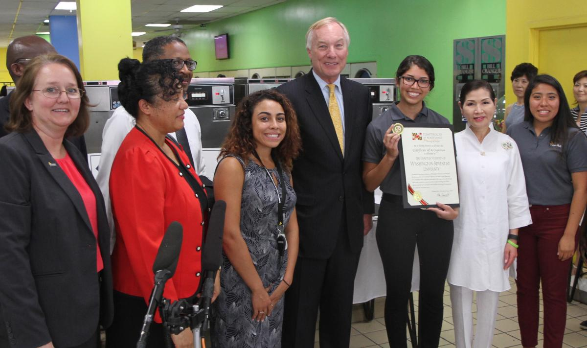 Washington Adventist University faculty, staff and students join Peter Franchot, comptroller of Maryland (center) and Yumi Hogan, the first lady of Maryland (second from right), at Rainbow Coin Laundry for a Sam's Club award ceremony.