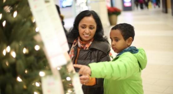 A mom and her son pick a child to sponsor from the Angel Tree.