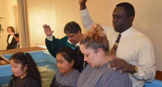 Pastor Pedro Simpson baptizes the Martinez family as  evangelist Julio Chazarreta looks on