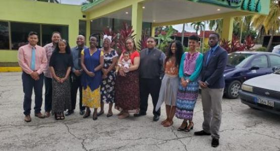 Sandro Miranda, Youth Ministries Director Jason Ridley, Courtney Cantrell, Carl McClatchie, Blissa Letang, Deja Dockery, Young Adult Ministries Director Charde Hollins (holding Addie Joy), Matthew Scone, Brittany Cantrell, Tara Carmen and Tanitoluw Ajaiyeboa stand in front of a church in Cuba where they preached.