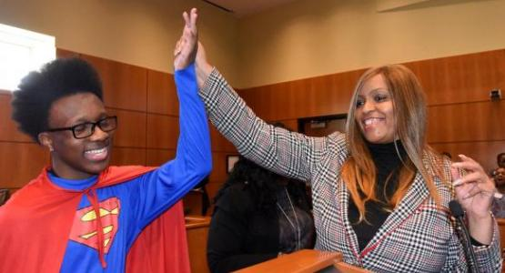 """Lorene Watkins, Mt. Olivet's Relationship Ministries leader, gives a high five to a fifth-grader from a local public school who played the """"Superman"""" defendant during a mock trial. Photo by April Saul"""