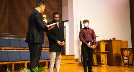 Pastor Sanghae Kim reads the baptismal vows to candidates Kyle Williams and Joseph Berry.