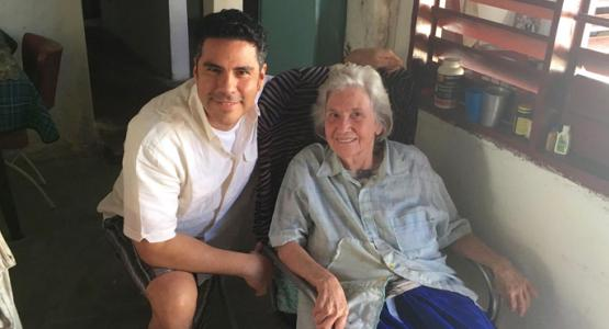 Pastor César González visits with Cenaida Fort Defaus, a Cuban member who opens her home as a meeting place for her church.