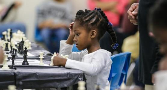 Nia Burton, BJA kindergartener, concentrates before she makes her next move at the chess tournament.