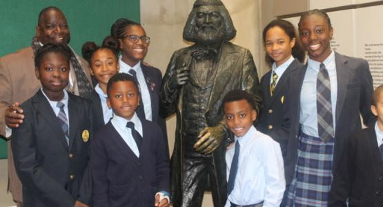 George E. Thornton, Sr., principal of the Dupont Park Adventist School, and eight students (left of the statue) Imani Yates, Simone Scott, Ayanna McInnis, Christopher Henderson, (right of the statue) Chase McClure, Jaffe Watkins, Dorian Donovan and Lawrence Talbert stand next to a Frederick Douglass statue.