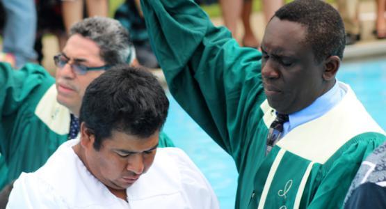 Peter M. Simpson, coordinador de los ministerios hispanos en la Asociación de Ohio, bautizando a Salvador Hernández, un nuevo miembro de la iglesia hispana de Hamilton