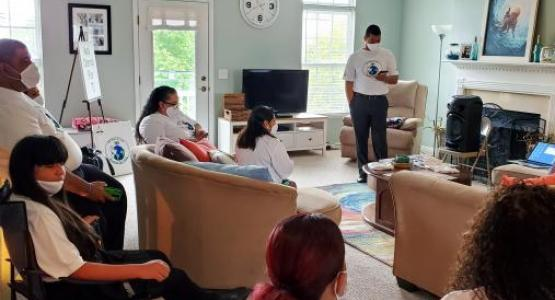 Elder David Santiago opens his home for members of the Lorain Hispanic church plant, as Pastor Anthony Infantes (pictured standing) shares the Word of God.
