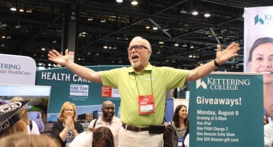 Victor Brown, decano de admisión de Kettering College en Kettering, Ohio, repartiendo premios en el salón de exposiciones.