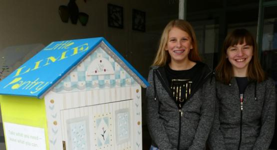 Kate Sharbaugh and Emma Schartner stand with one of their pantries.