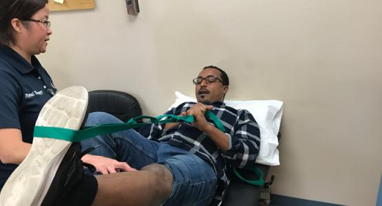 Lynda Hiponia, a physical therapist with Adventist HealthCare Rehabilitation, helps fire survivor Memar Ayalew regain strength and mobility in his leg.