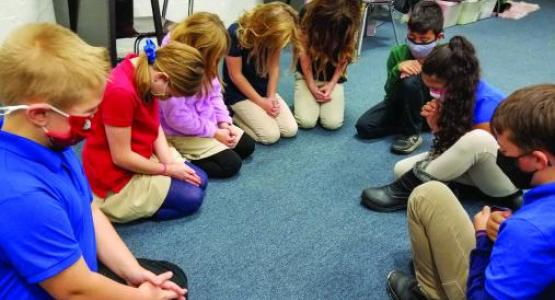 Students from the Mountain View Christian School in South Williamsport pray together.