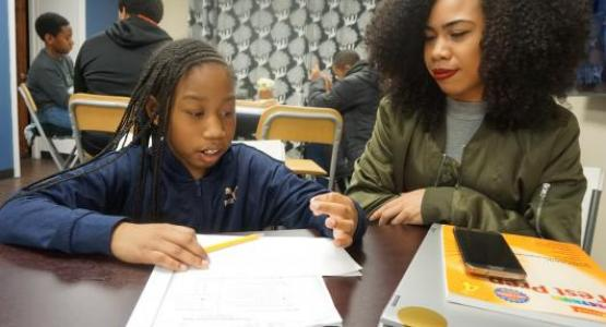 Amy Thomas, a student at Temple University, tutors third-grader Jodi Glenn as part of the REACH Success after-school program.