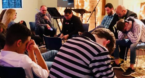 """Edward Marton, Ohio Conference's Youth Ministries director, leads prayer with high school students and youth pastors during the """"ReCharge"""" event at the Worthington church."""