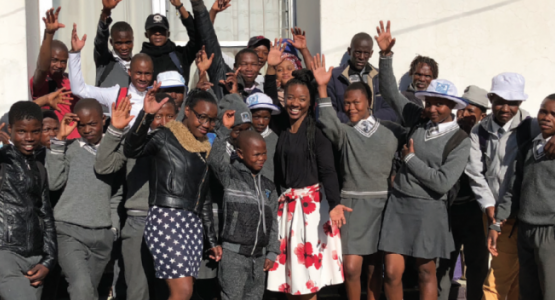 Sidney Harris (white skirt), a member of the Ephesus church in Richmond, Va., waves hello with a group of students who decided to get baptized as a result of Harris' ministry in Lesotho.