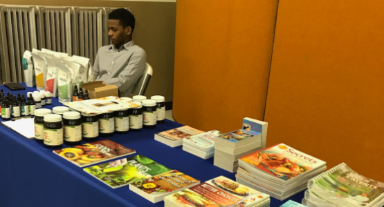 Wellness instructor Ezra St. Juste staffs the natural remedy literature display table at the Community Health Expo.