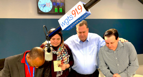 Morning show hosts Jerry Woods and Blanca Vega, General Manager Kevin Krueger and morning show producer Spencer White pray during a break.