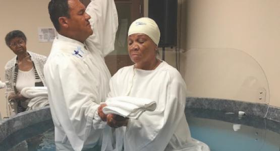 Stephen D. Lewis, pastor of the Dayton church, baptizes Brenda Rutledge.