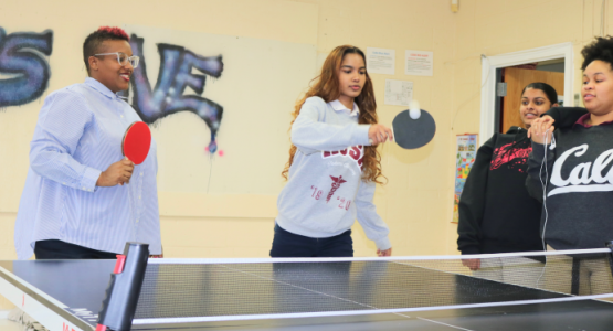 """Chaplain B. Leah (left) and students Sherina Moses ('20), Valerie Ganta ('22) and Yannice Prather ('20) play a friendly game of ping-pong in the """"The Living Room."""""""