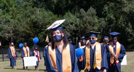 """Graduate Tricia Biton, along with her classmates, march in to """"Pomp and Circumstance."""""""