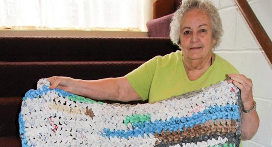 Shirley Crouser shows a soft mat made from colorful plastic grocery bags which will bring warmth to a homeless person.