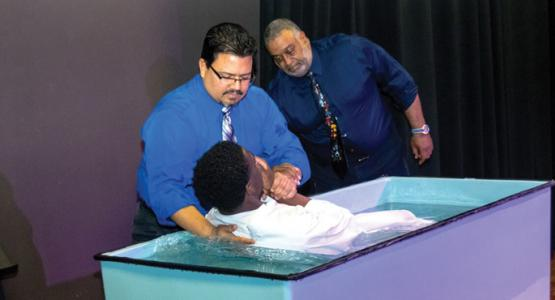 Luis Camps baptizes senior Christopher Cadet. Photo credit: Ross Avery Gordon