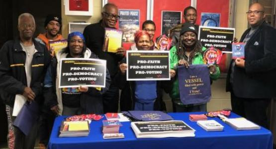 """Jerome Hurst, pastor of the Southeast church, and a team of canvassers display """"pro-voting"""" signs prior to Election Day."""