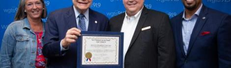 """Mayor Bridget Newton (left), and councilmembers Sidney Katz and Will Jawando (right), declare August 23, 2019, """"WGTS 91.9 Day,"""" awarded to President and General Manager Kevin Krueger (second from right)."""