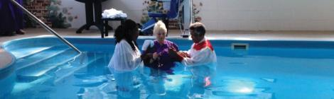 Rosalind Beswick and Carl Rogers help Susan Riddle (center) prepare for her baptism.
