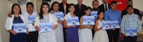 New members (front row) display their baptismal certificates.