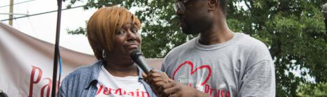 Event organizer Roland Blackman talks with a woman from the community.