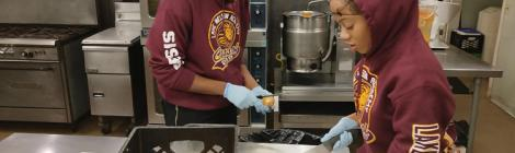 Seniors Lyden Stanislaus-Niles and Taylore Williams help cut onions at Elijah's Promise Community Kitchen.