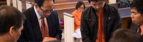 Pastor Steven Rantung prays with members grappling with immigration issues