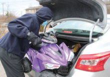 A volunteer places a toy in a car to bring joy to a child.