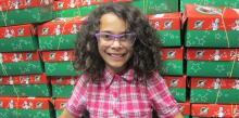 Project director Adilynn woods poses with the completed shoeboxes.