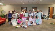 Twenty-one experienced- and beginner-student sewers, including co-leader Dorcas Sweeny (left), display some of the 120 pillowcases they donated to a local nursing home.