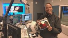 Morning show host Jerry Woods holds up a purse given to him by his sponsored child's mom.