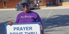 Church member and praise leader Ellen Boakye-Dankwa invites drivers for a quick prayer.