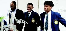 Physics and Robotics coach Courtney Brown, and seniors Cole Mattox and Joshua Perkins display their robotics project.