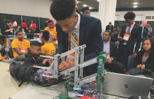 Fundamental of Engineering student Solomon Hill makes adjustments to his robot minutes before a competition.