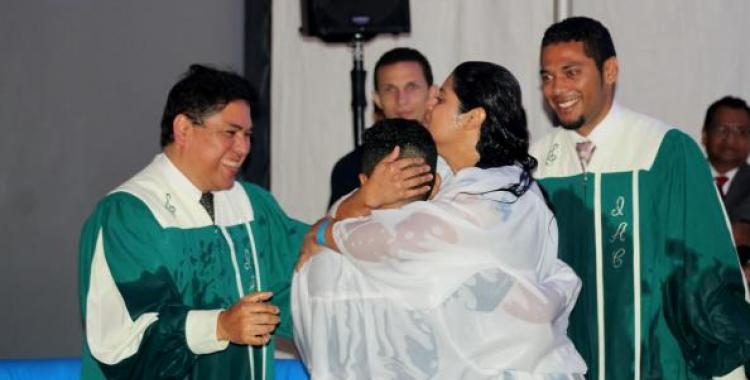 Lail Fuentes (left), pastor of the First Columbus Spanish church, and Enmanuel Freites (right), pastor of the Dayton Spanish church, baptize one of five people during the 2018 Ohio Conference Hispanic Camp Meeting.