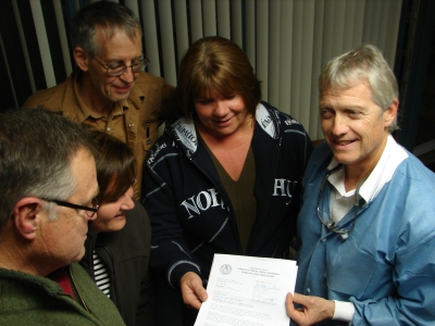 Pastor Clinton Adams, Judi Hayes, Bill Tingler, Ida Minter and Hollis Wolcott review the FM license they received earlier this year for their new station.