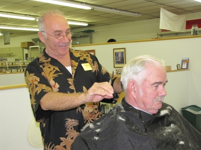 Phil cuts Pastor Farley Blankenship's hair. The pastor is one of his regular customers from the community.