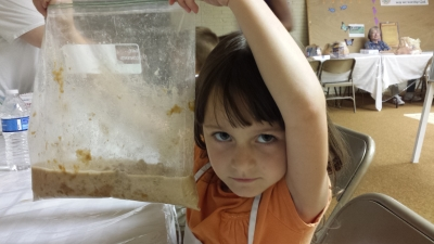 Tisha, 6, holds up a work in progress—whole wheat bread in a bag.